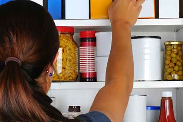 Woman neatly organizing her pantry and items on shelves