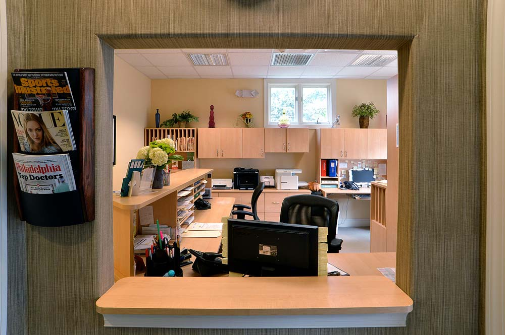 Medical office reception window with custom built furniture and cabinets