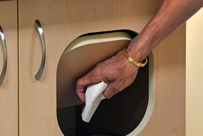 Dentist throwing out trash in custom built cabinet