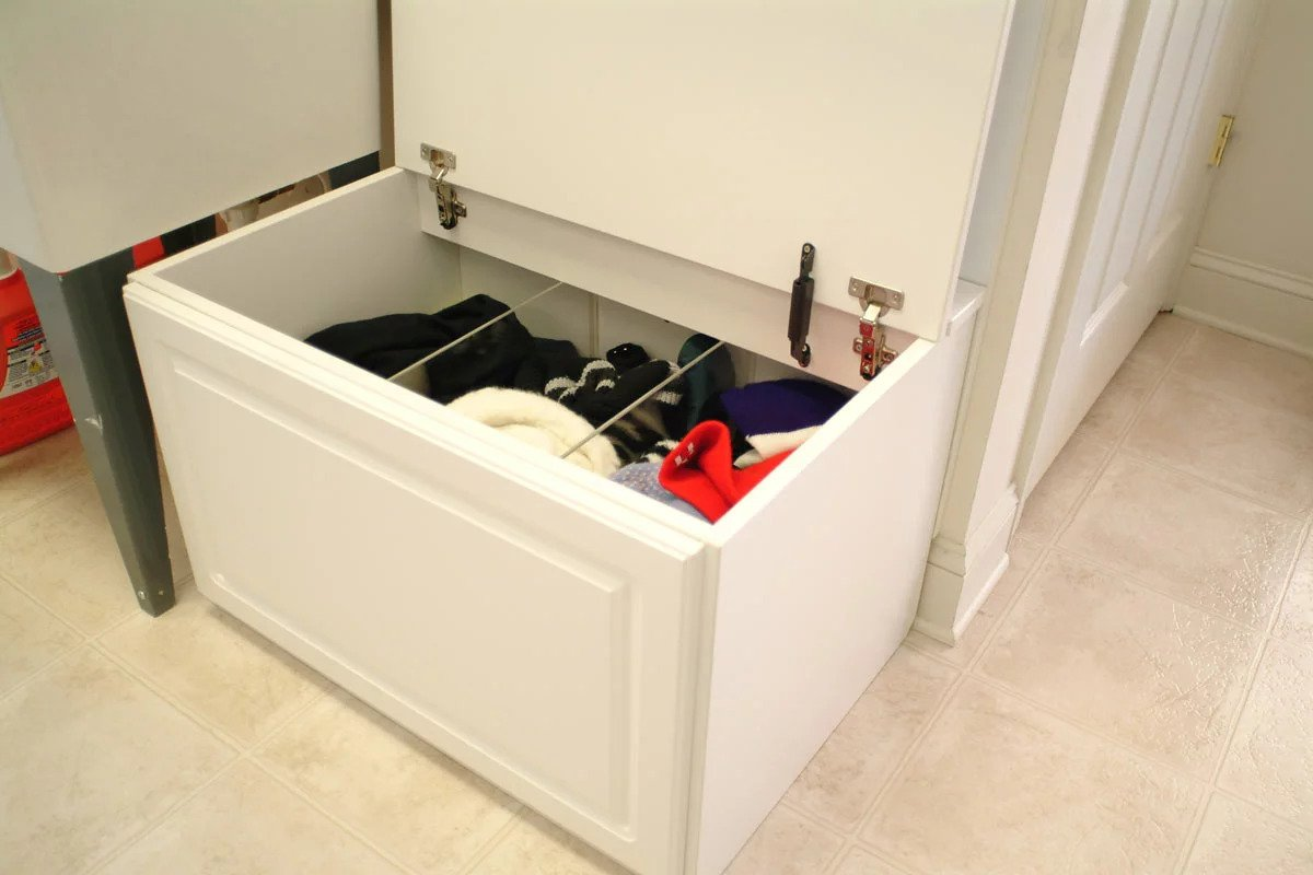 Additional storage chest or drawer unit filled with seasonal items which include hats and scarves