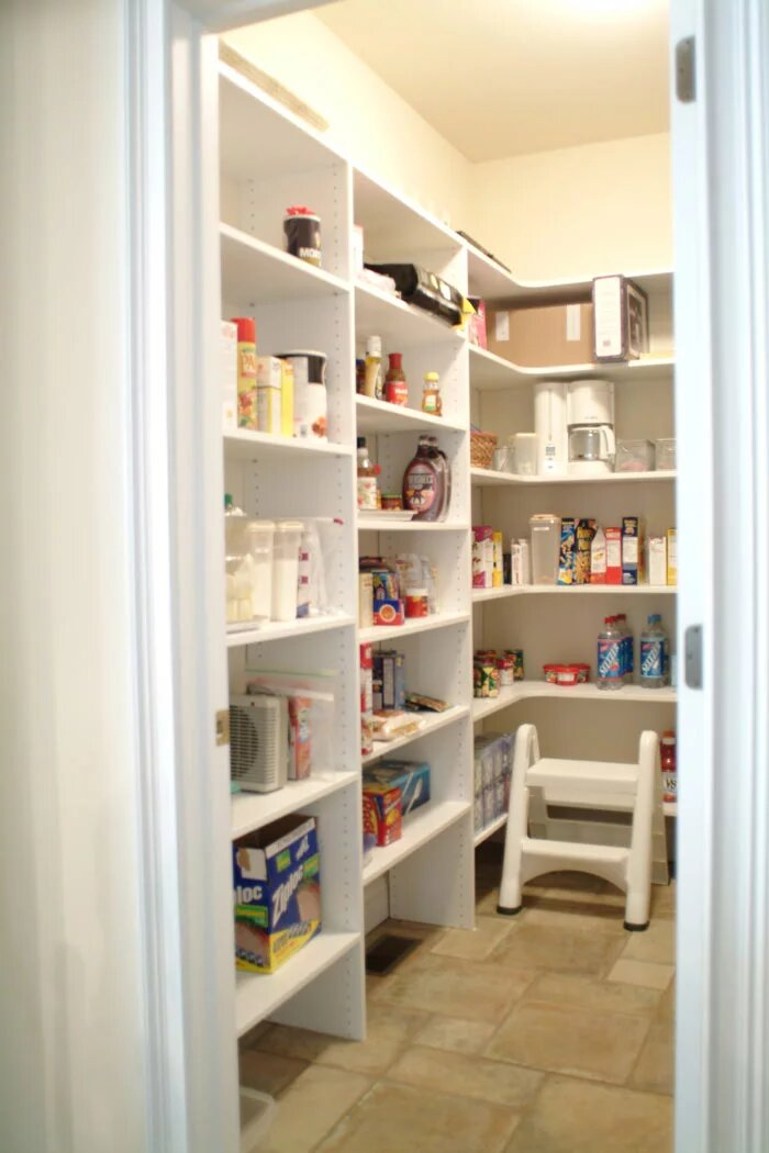 Walk in pantry with white wood finish and corner shelves