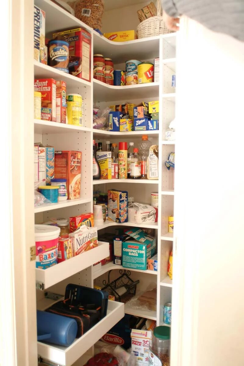 Walk-in pantry with food items organized on slde out shelving