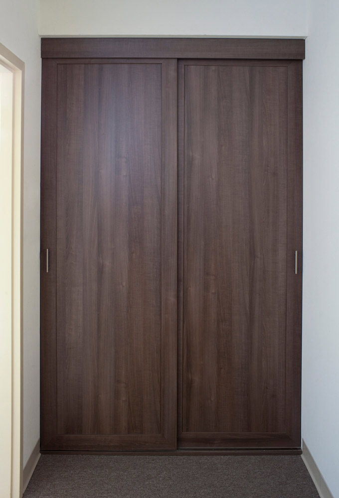 Small hall closet with solid wood sliding doors