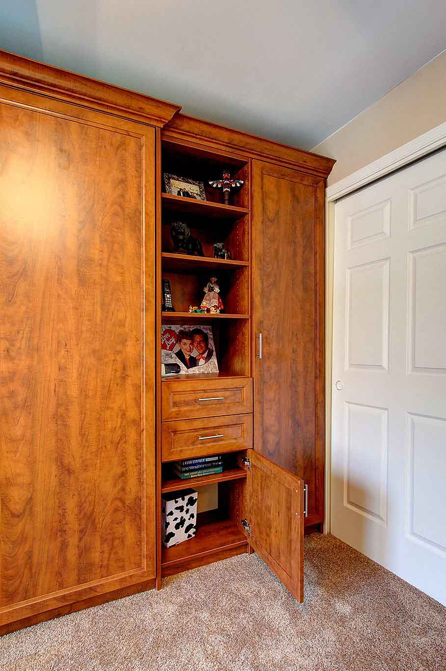 Organized drawer storage in a furniture cabinet next to concealed queen sized Murphy bed