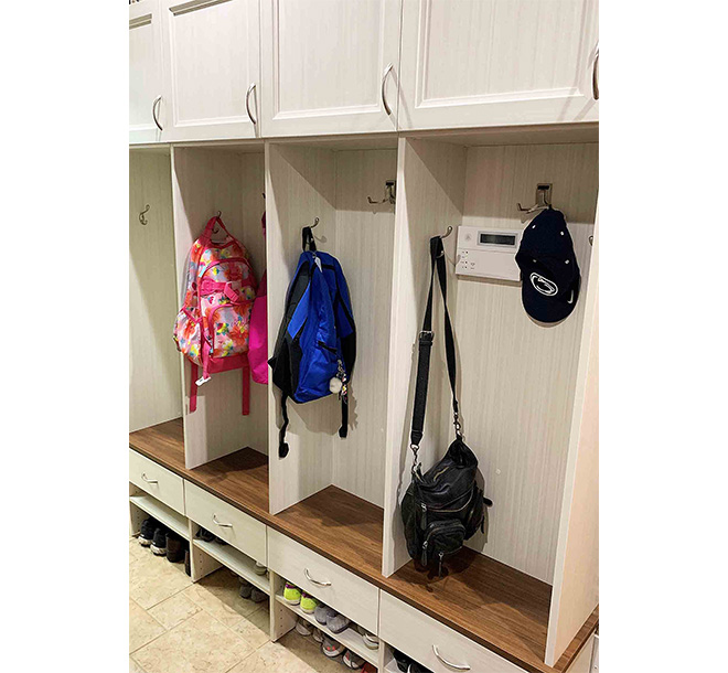 Custom mudroom design with cubbies and bags neatly hung and organized