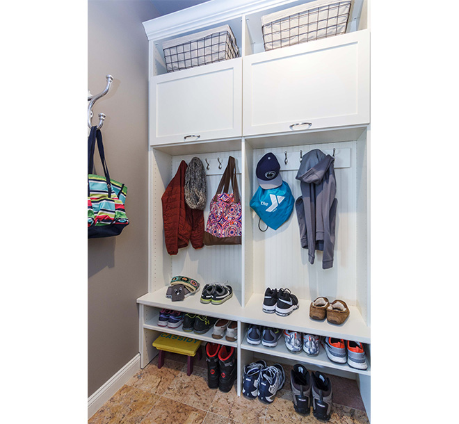 Mudroom with childrens clothing items and accessories hung and neatly organized