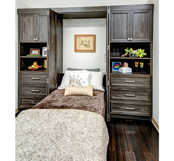 Custom twin sized wall bed pulled down from a wall cabinet