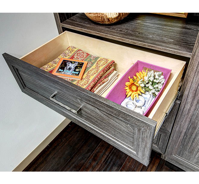 Open cabinet drawer on wall bed unit with neatly stored and organized items