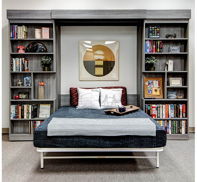 Custom wall bed pulled down between sliding bookshelves