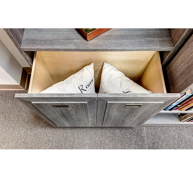 Deep cabinet drawer slid open storing and organizing pillows and bedding items