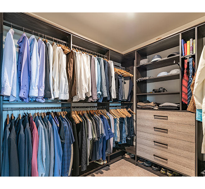 Mens clothing hung and organized neatly in walk in closet