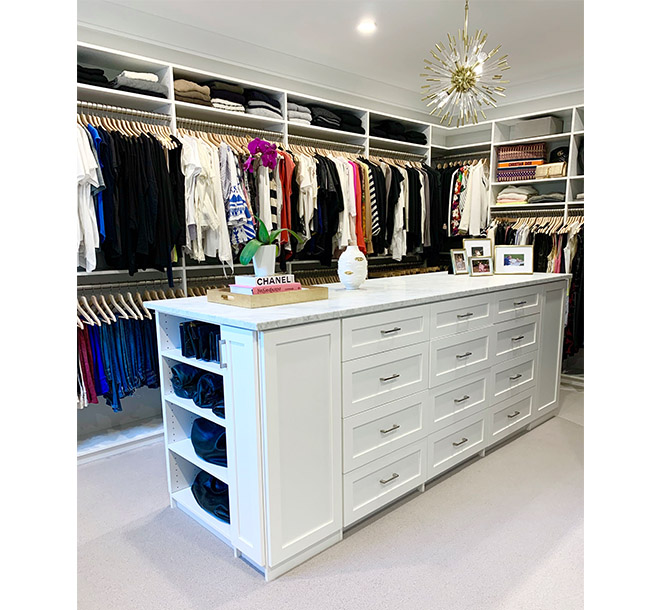 Beautiful white walk-in closet with center island and granite countertop