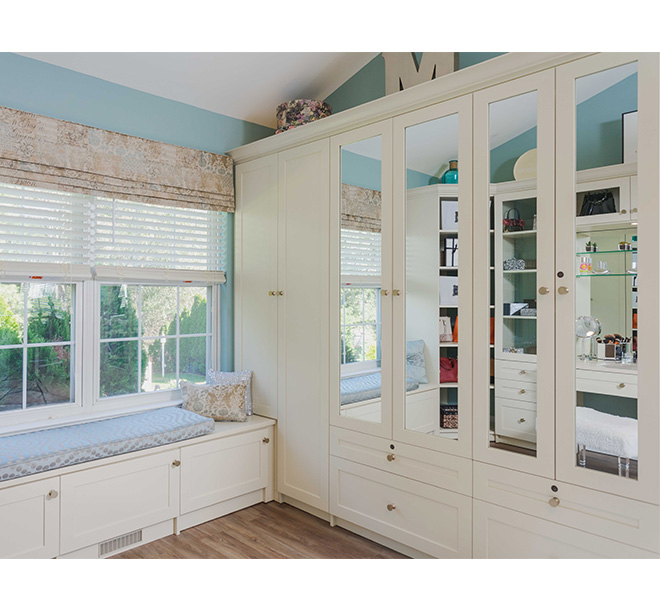 Dressing room with a sitting bench and beautiful cabinets