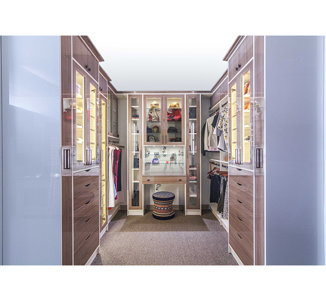 Custom walk-in closet finished in high gloss with vanity and sitting area