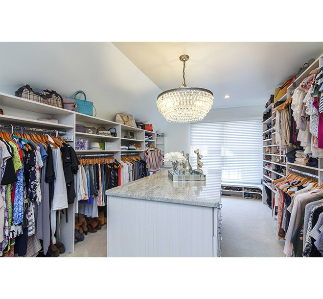 Traditional chic walk-in closet with center island finished in white chocolate