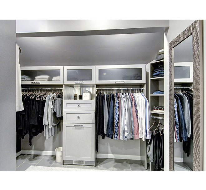 Walk-In closet neatly organized with closed storage and center cabinets