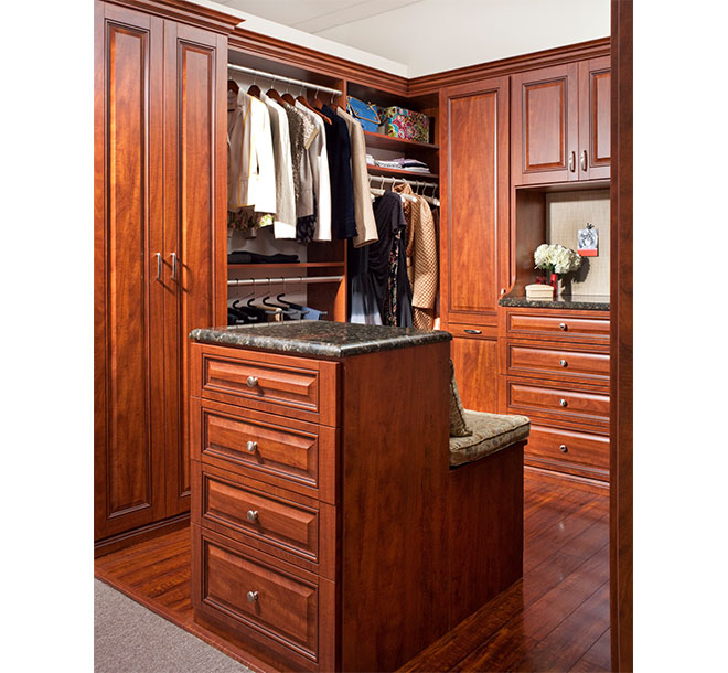 Walk-in closet with center island and bench seat with pillows