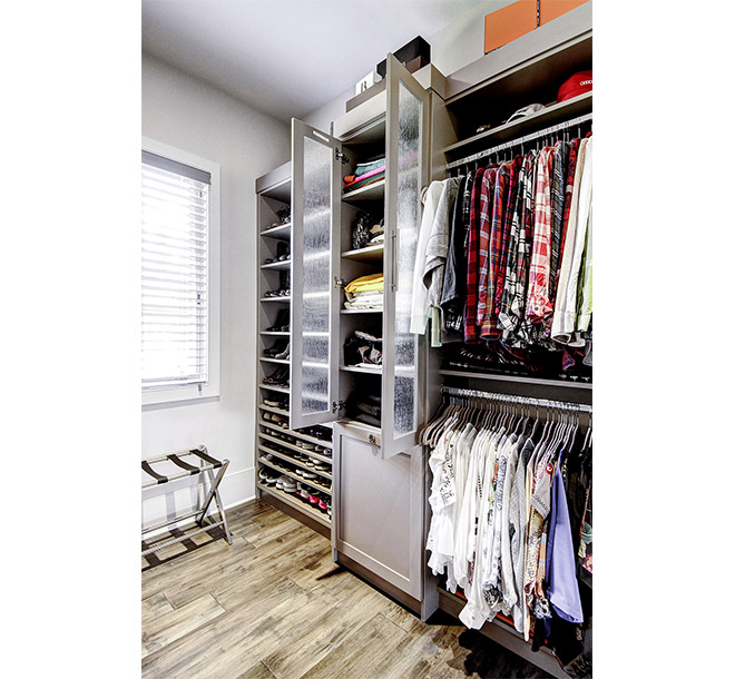 Custom closet shaker style doors with rain glass inserts housing folded clothes