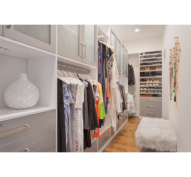 Walk in closet with custom shoe shleving and pull out vallet bar