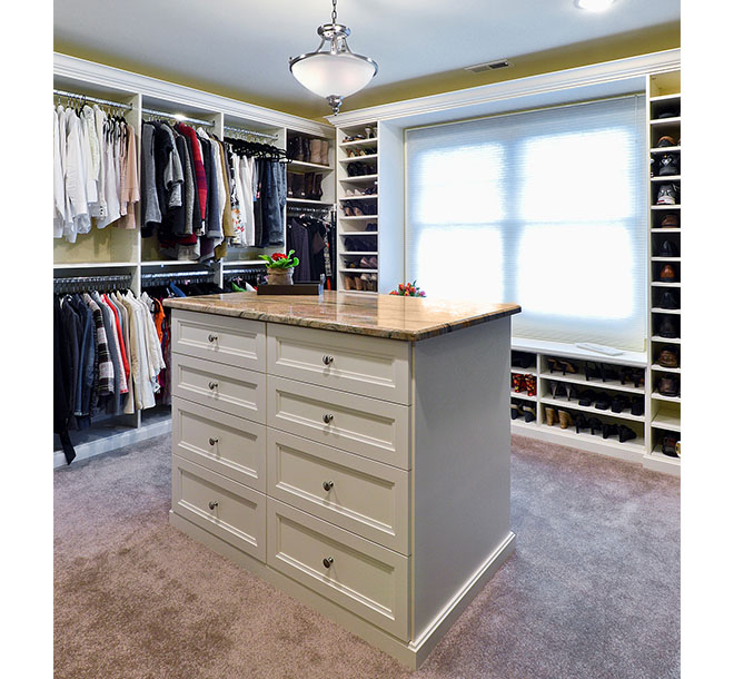 Beautiful walk-in closet with center island featured through double french doors