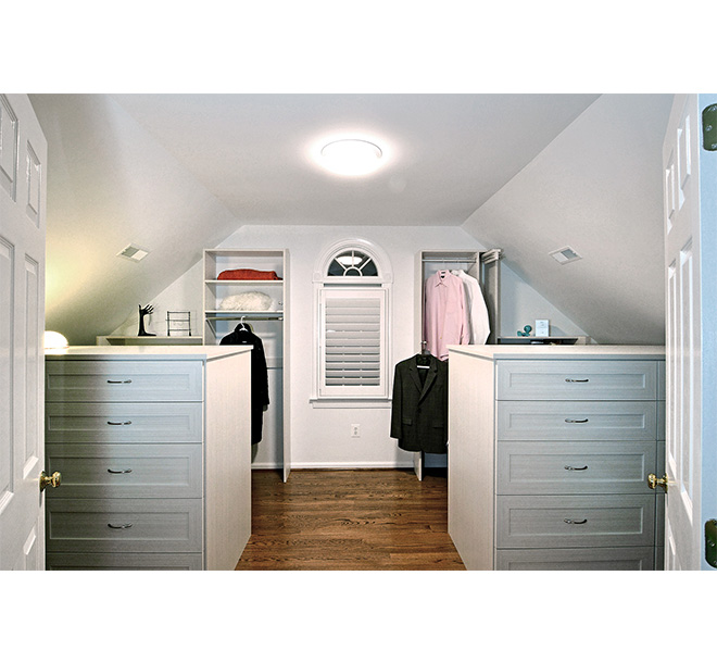 Walk-in closet with two custom furniture cabinets spaced evenly apart
