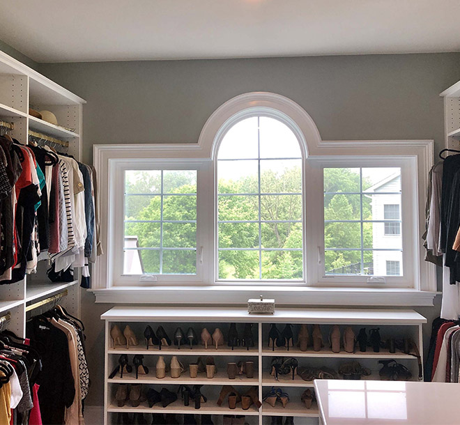 Walk in closet with shoe storage under picture window