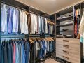Mens walk-in closet space with double hanging and custom shelves