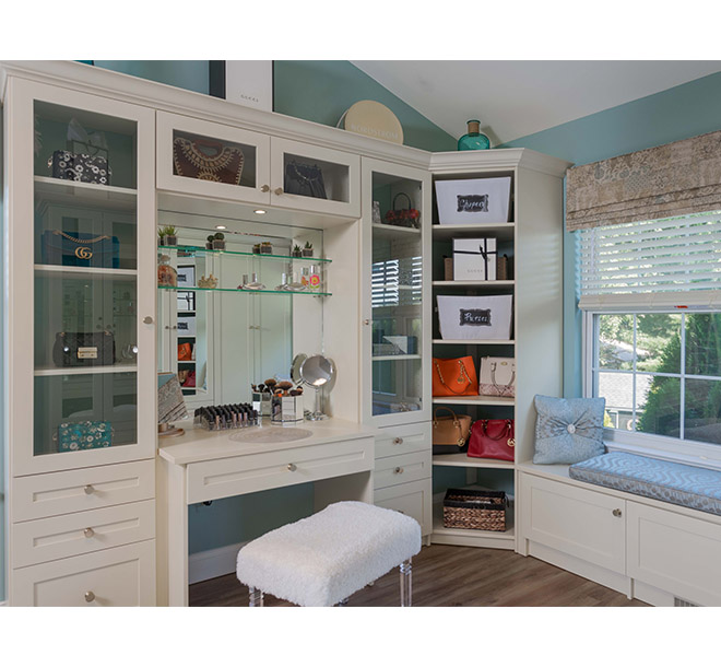 walk-in closet with corner shelves and glass door inserts