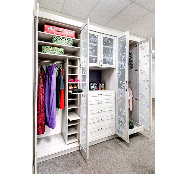 Wardrobe closet with clothes neatly hung on hangers and pull out shoe shelving