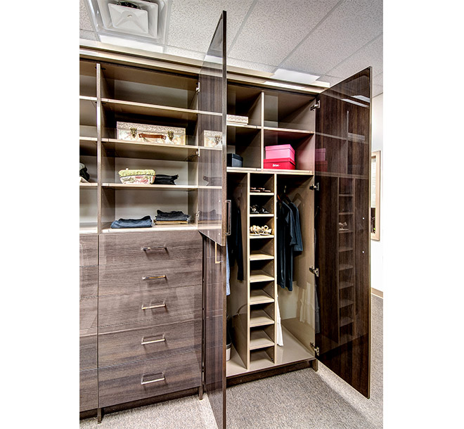Custom wardrobe closet with doors open displaying adjustable shelving and cubbies