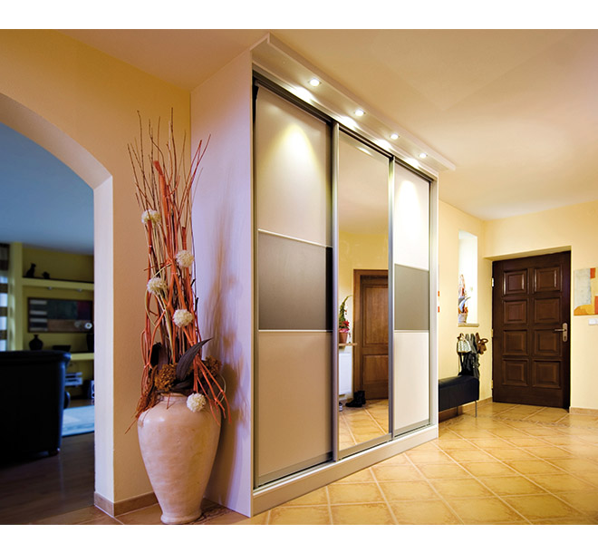Custom wardrobe with sliding glass doors and built-in lighting