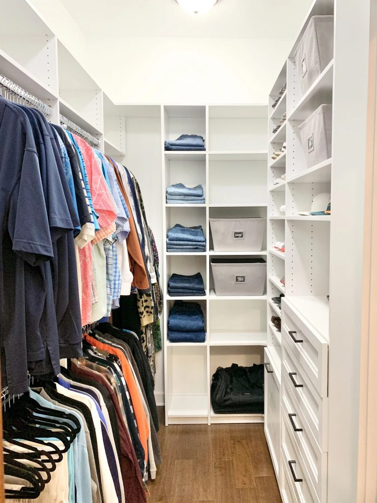 Men's closet organized with double hanging and open shelving