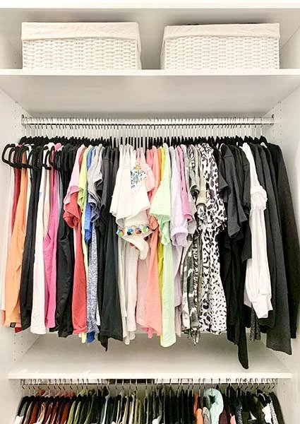 Womans clothing organized in closet space