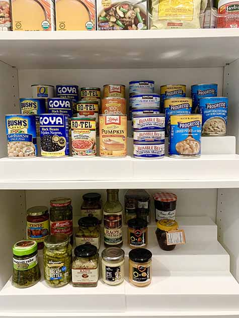 Canned goods organized on pantry shelves with risers