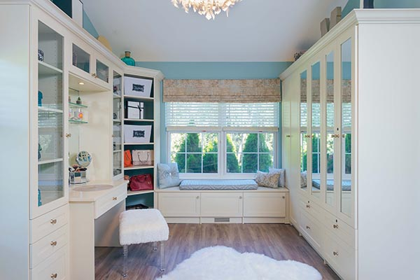 Walk in closet with vanity and mirrored doors