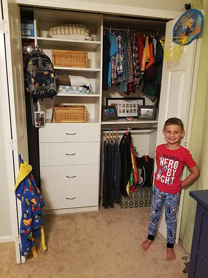 Boy standing by his organized closet system