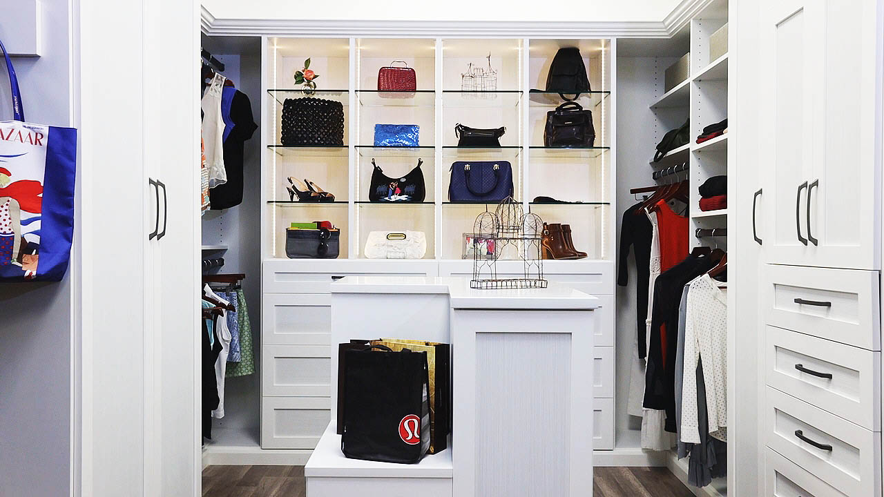 Organized walk-in closet with glass shelves and center bench area