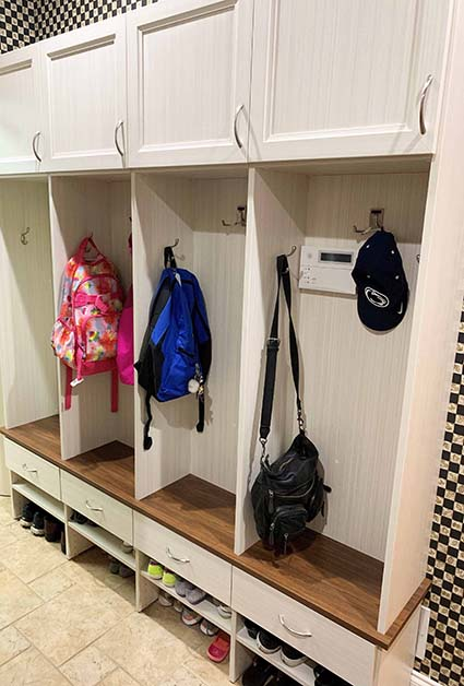 Organized mudroom with bags hanging and shoe storage underneath benches