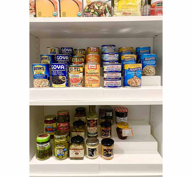Canned good organized by risers on pantry shelf