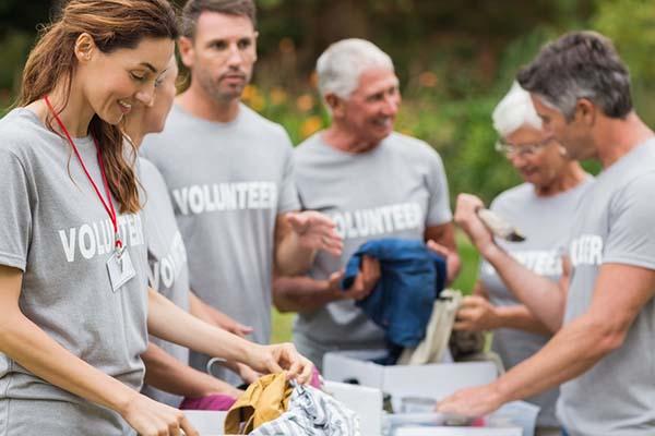 Happy volunteers looking through donation box