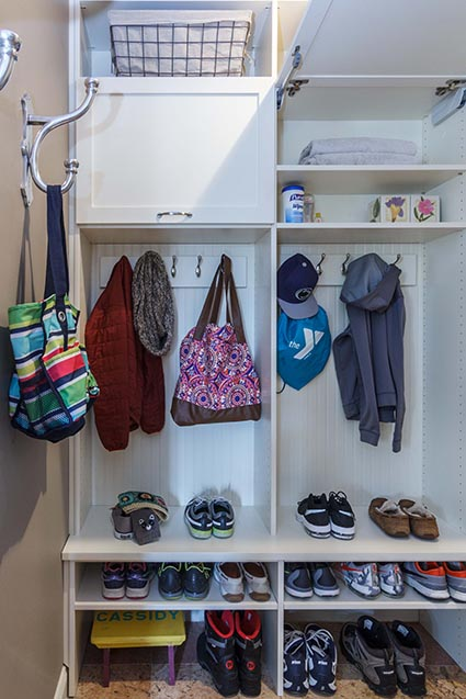 Organized mudroom with jackets hanging and baskets for storage