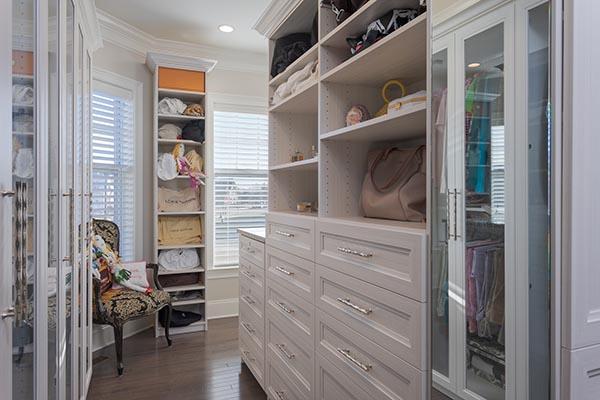 Walk-in closet with custom built cabinet between windows