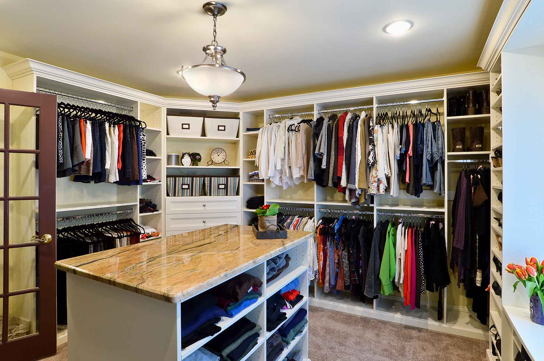Organized walk-in closet with seasonal clothing