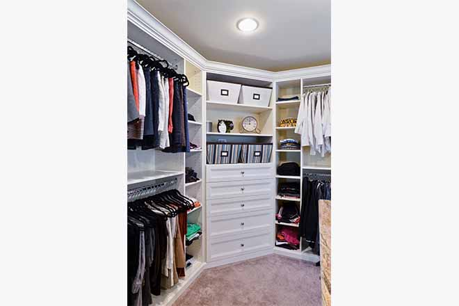 Organized closet with double hanging and custom shelving holidng clothing