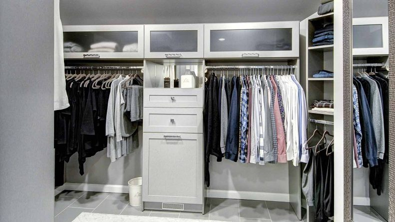 Organized clothes stored in walk in closet system
