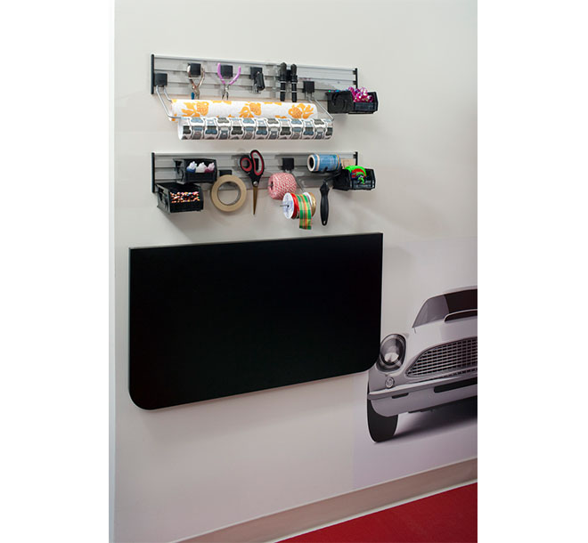 Folded down countertop with arts and crafts supplies hung above