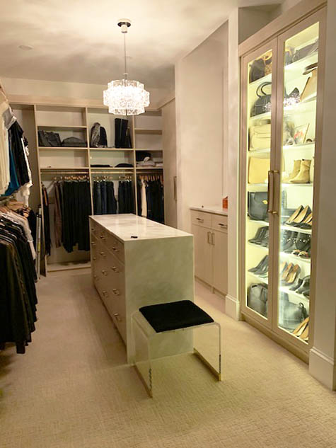 Walk in closet organized with glass doors and lighting