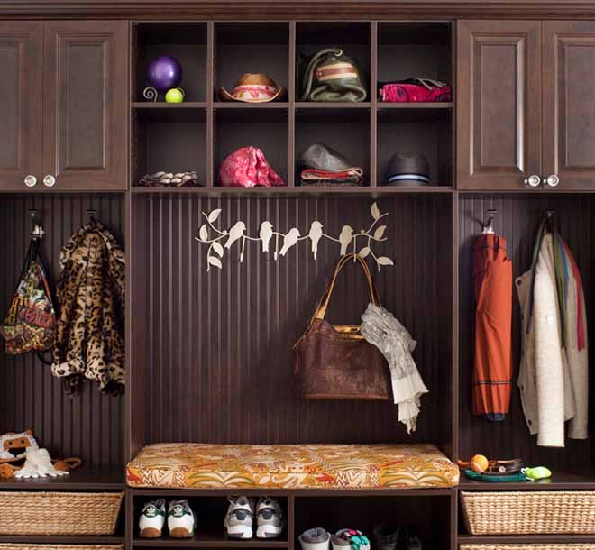 Entryway cabinet with bench and hooks neatly organizing coats and bags