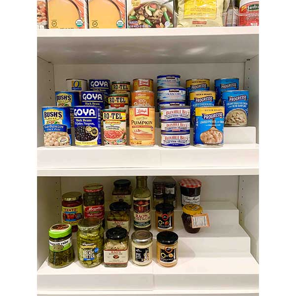 Food items stored on pantry shelf risers