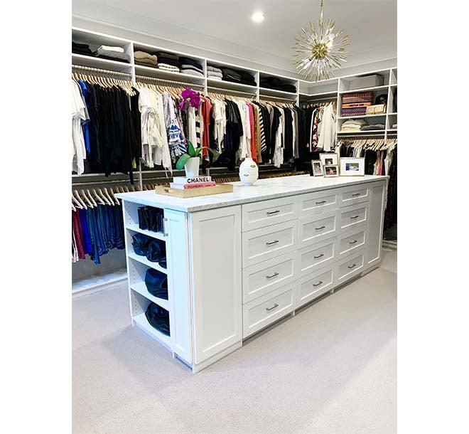 Beautiful white walk-in wardrobe closet with center island and granite countertop